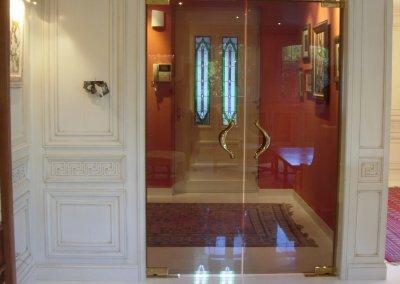 Double porte en verre va-et-vient incorporée dans boiserie de style