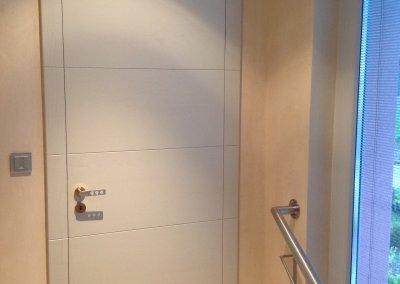 Porte intérieure contemporaine, ébrasement et battants en frêne massif, rainurage horizontal du battant à l'ébrasement. Charnière invisible (Tectus) et serrure magnétique, laqué gris, pores ouverts